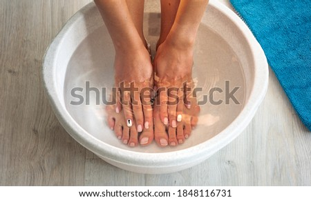 Woman put hands and feet in bath with hot water and baking soda at home. Homemade bath soak for dry feet skin Stock photo ©