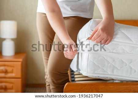 Woman put on new clean mattress pad on orthopedic mattress corner. Bed linen at home. Sheet is worn on soft clean mattress. Protection from dirt washed linens mattress pad in bedroom interior.