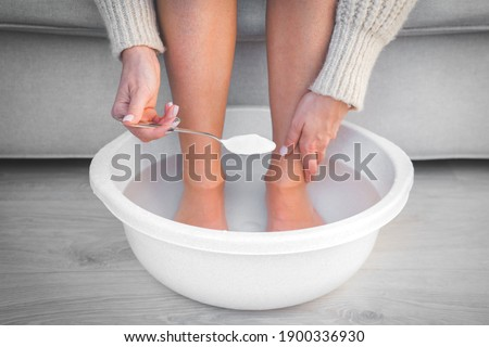 Woman put spoon of baking soda in bath with hot water for her feet. Homemade bath soak for dry feet skin.  Stock photo ©