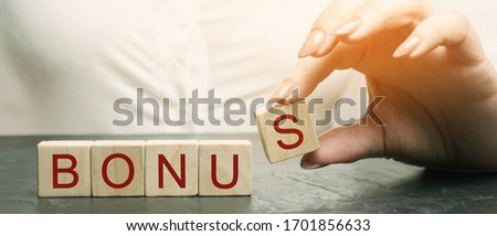 Woman puts wooden blocks with the word Bonus. Receive bonuses, rewards and preferences. Getting benefits and extra points. Bonus wage for holidays. Benefit, cashback. Business concept