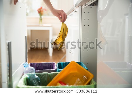 Woman putting banana peel in recycling bio bin in the kitchen. Person in the house kitchen separating waste. Different trash can with colorful garbage bags.
