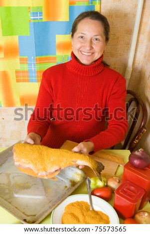 woman putting  breaded fish to cook griddle