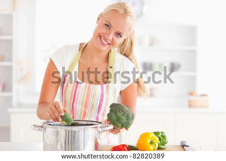 Woman putting cabbage on water while wearing an apron