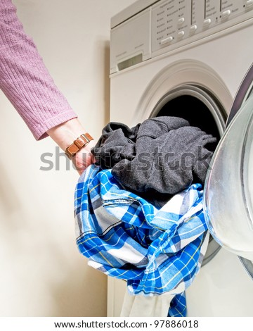 woman putting clothes in washing machine to clean