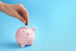 Woman putting coin into piggy bank on light blue background, closeup. Space for text