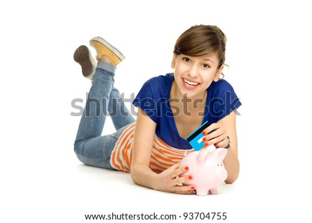 Woman putting credit card into piggy bank