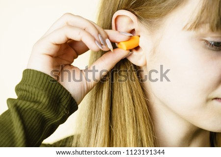 Woman putting ear plugs into her ears getting rid on noise in loud place. #1123191344