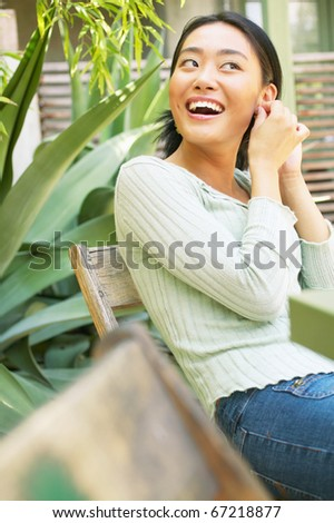 Woman putting earring in outdoors