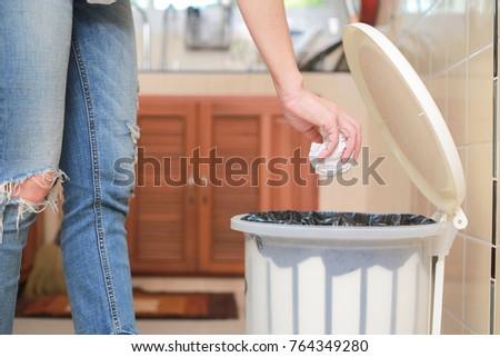 woman putting empty plastic bag ...