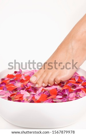 Woman putting feet in bowl of flower petals
