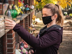 Woman putting grave candle lantern at the columbarium wall in the cemetery on All Saints' Day. Remembering her relatives who died. Wearing protective face mask against COVID-19 Coronavirus pandemic.