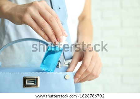 Woman putting hand sanitizer in purse on light background, closeup. Personal hygiene during COVID-19 pandemic Foto d'archivio ©