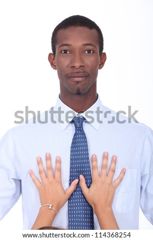 Woman putting hands on businessman's chest