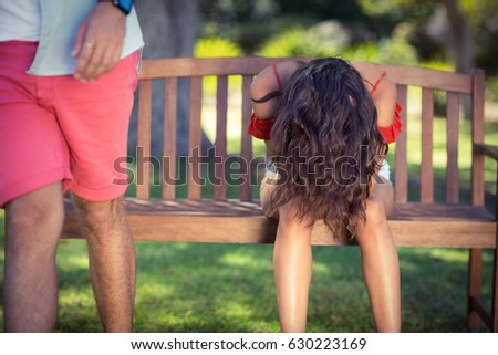 Woman putting head down after argument in park