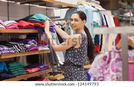 Woman putting jumpers on shelf in boutique