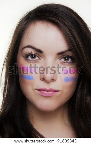 woman putting lines under her eyes as if ready for war like