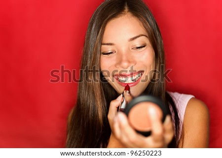 Woman putting makeup lipstick. Asian girl putting lip gloss red lipstick smiling happy looking in pocket mirror. Beautiful young mixed race Asian / Caucasian on red background.
