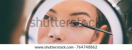 Woman putting mascara makeup in mirror banner at home bathroom morning routine. Beautiful Asian girl getting ready applying eye make-up with brush. Closeup on eye in reflection.
