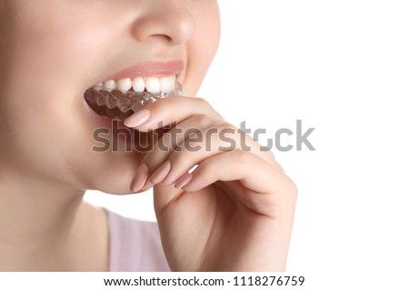 Woman putting occlusal splint in mouth on white background, closeup
