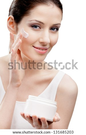 Woman putting on lifting cream from container on face, isolated on white. The pursuit of beauty