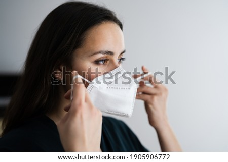 Woman Putting On Medical N95 Face Mask