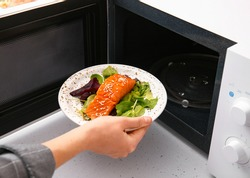Woman putting plate with food in microwave oven