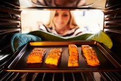 Woman Putting Salmon Fillets Into Oven To Cook