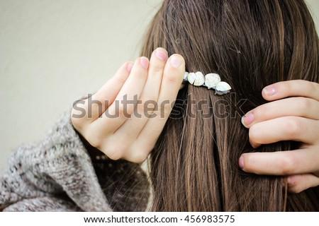 Woman putting sea marine themed jewellery hair pin into brunette hair closeup Stockfoto ©