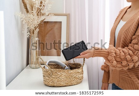 Woman putting smartphone into wicker basket with gadgets at home. Digital detox concept