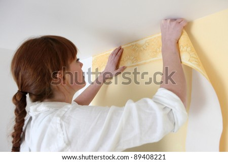 Woman putting up a wallpaper border - stock photo