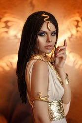 woman queen Cleopatra art photo. Creative golden makeup Black hair braids. Carnival ethnic egypt costume dress. Accessories jewelry snake bracelet, crown. Fashion model girl beautiful face close-up