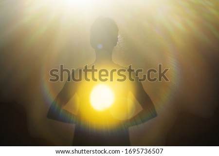 Woman radiating light from within into an opening of spiritual heart.