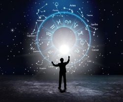 Woman raising hands looking at the night sky. Astrological wheel projection concept