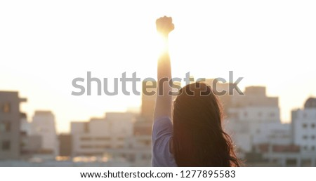Woman raising her fist in the air in victory stance