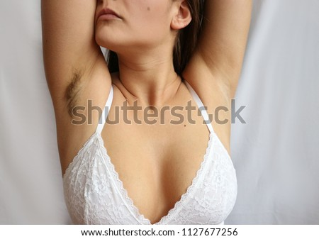 Woman raising her hands, one armpit shaved, the second is not, depilation and armpits care concept. Before and after shaving, hairy and clean armpit.