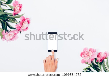Woman reach for screen of smart phone with her index finger among pink peonies on a white background, top view. Floral flat lay arrangement with flowers, and female hand touches blank display. #1099584272