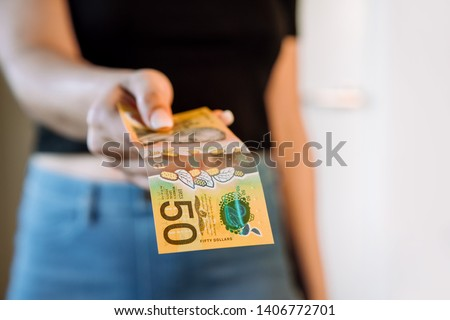 Woman reaching out hand to offer / pay money in Australian currency. Australian 50 (fifty) dollar note. #1406772701