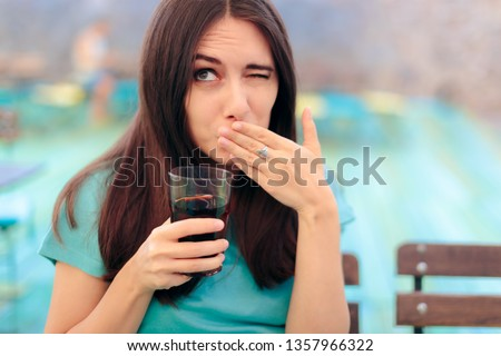 Woman Reacting after Having a Fizzy Soda Drink. Funny female customer in a restaurant having a carbonated beverage Foto stock ©