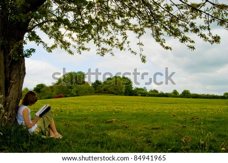 Woman reading a book against a tree in a meadow with grass, big tree and blue sky