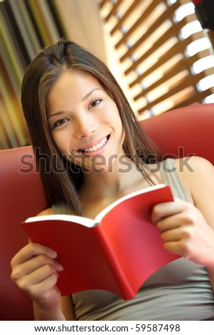 Woman reading a book at home. Young beautiful Caucasian / Asian female model