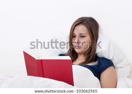 Woman reading a book in bed