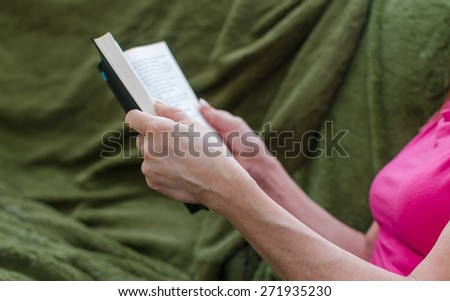 Woman reading a book on a green couch #271935230
