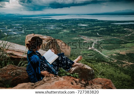 Woman reading a book on mountain,with the winter vacation of a woman is going to read a book and drink coffee,located on a cliff,it is what makes her feel relaxed after a hard work over many months #727383820