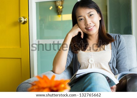 Woman reading a book on sofa in cafe restaurant