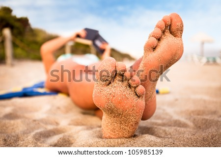 Woman reading a book on the beach.  Shallow deep of focus.
