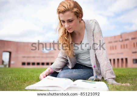 Woman reading a book while sitting on the lawn