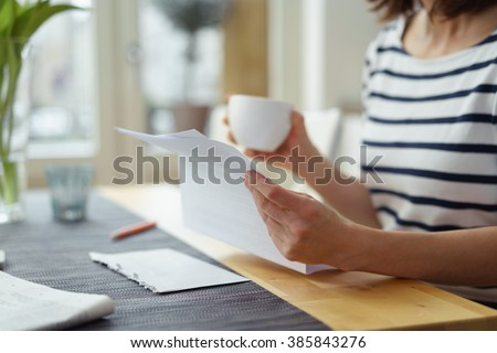 Woman reading a document at the dining table as she enjoys a morning cup of coffee, close up view of her hands #385843276