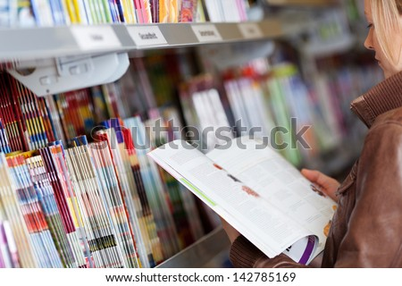 Woman reading a magazine which she has just removed for a display on a shelf in a supermarket Stockfoto ©