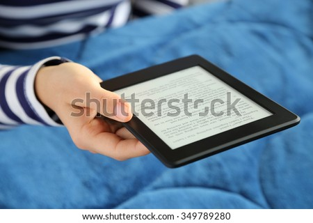 Woman reading a novel on a tablet in bed.
