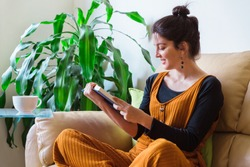 Woman reading a novel relax at home and drinking hot tea. Quarantine Indoor lifestyle. Horizontal side view of woman sit on the couch reading a book. Stay home concept. Leisure indoors entertainment.